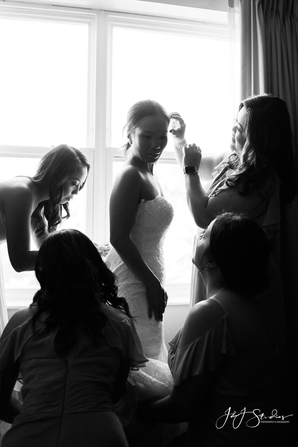bride and bridesmaids at window getting ready for wedding