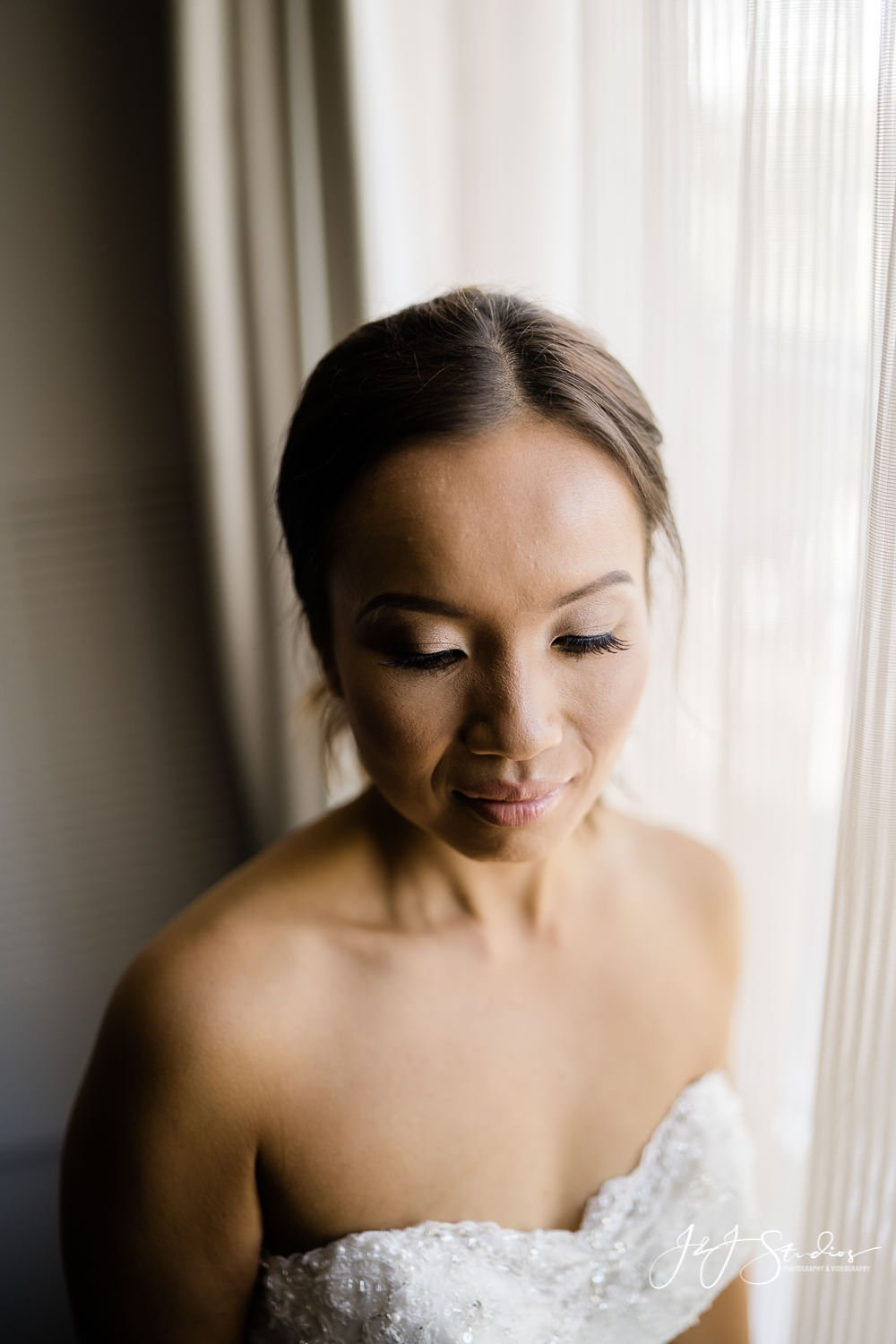 bride at window with eyes closed baltimore wedding photographer