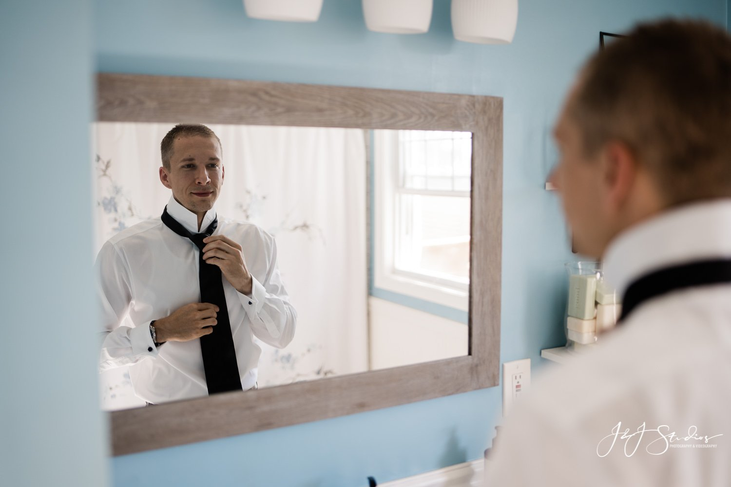 groom gets ready in the mirror baltimore wedding photographer