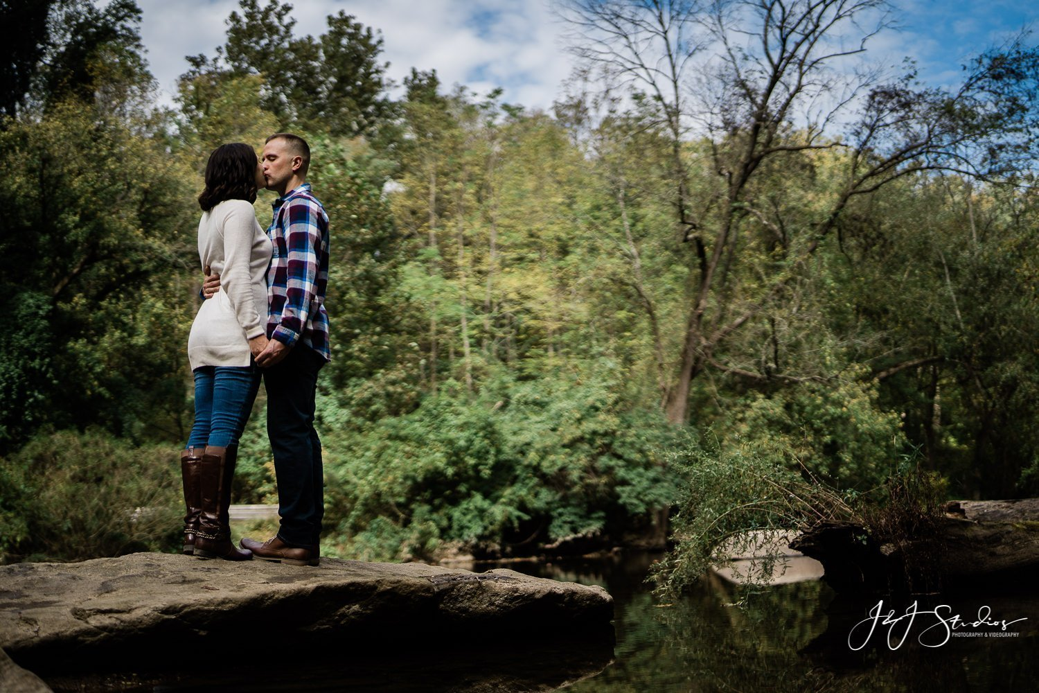 couple kissing next to creek
