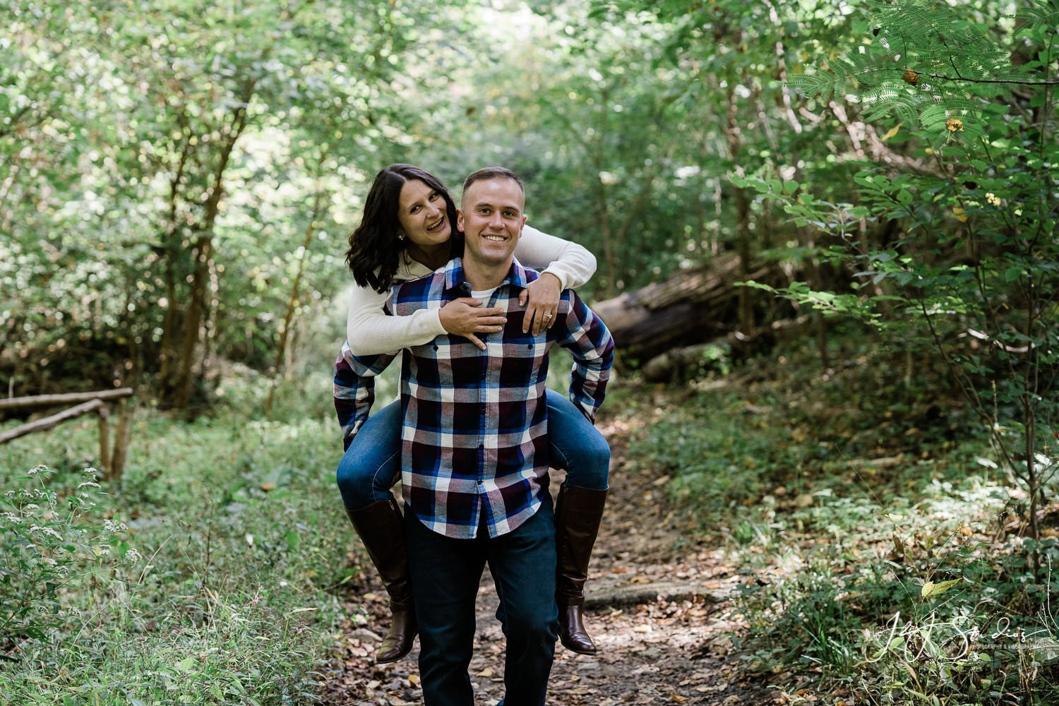 groom gives bride piggyback Wissahickon Park Engagement