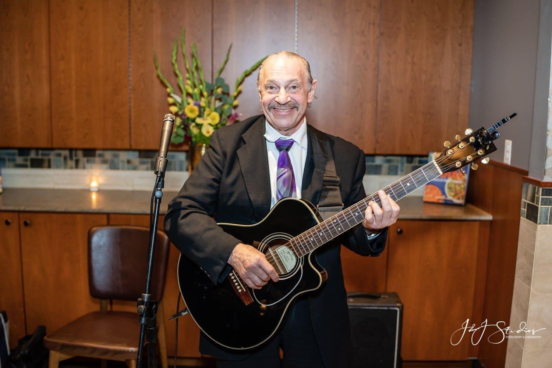 man plays guitar at jewish wedding at zahav