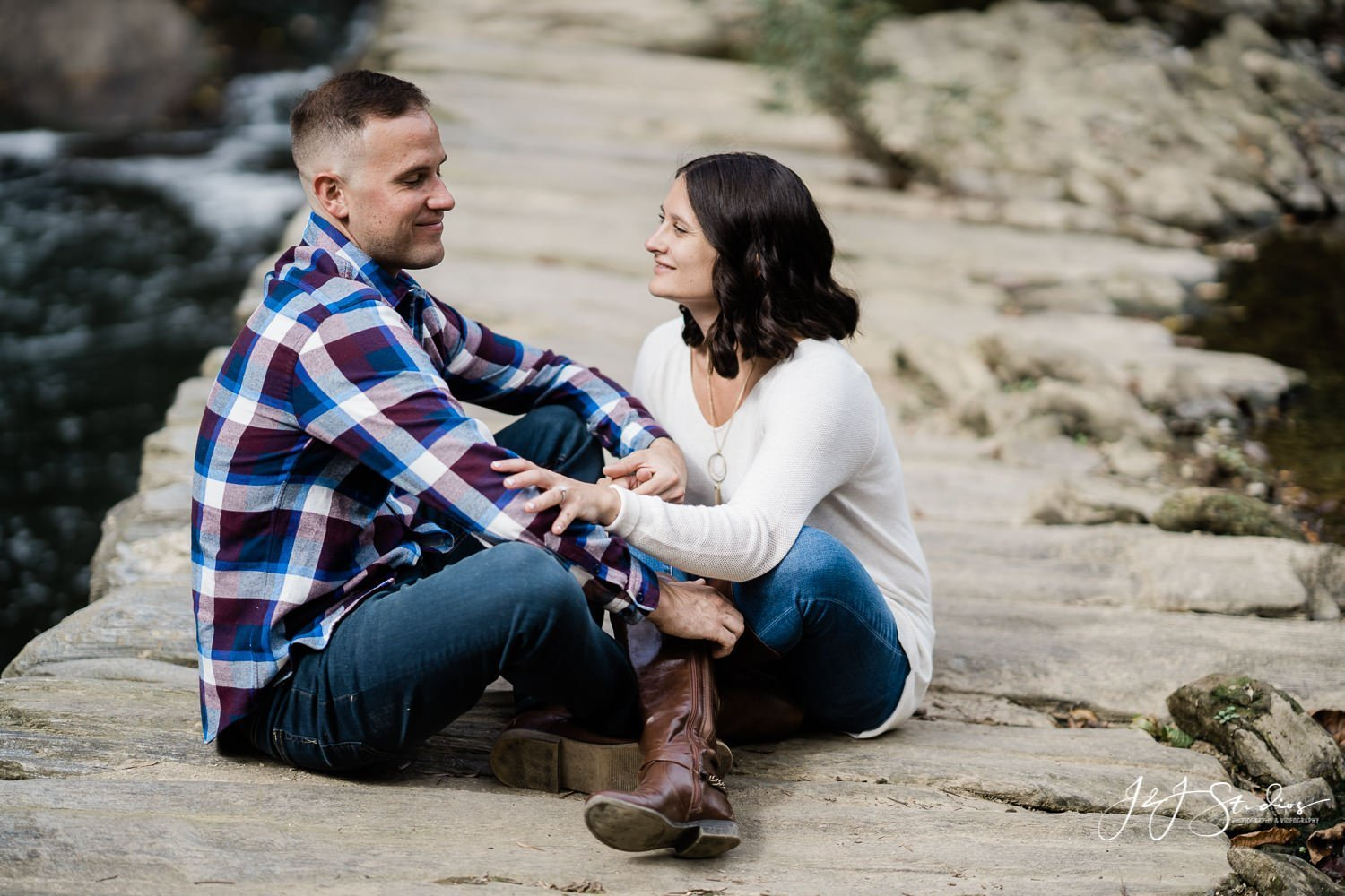 couple sitting indian style fall engagement