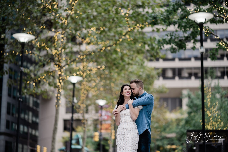 broad street couple kissing christmas tree lights in background philadelphia