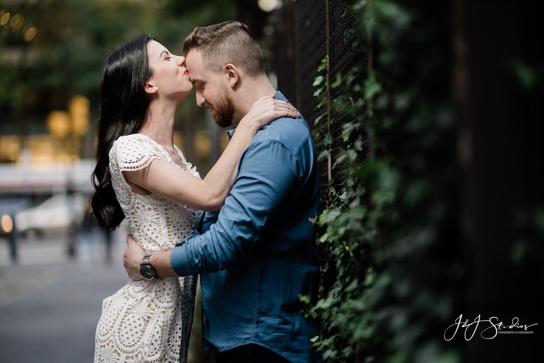 girl kisses her fiance on ivy wall philadelphia city hall
