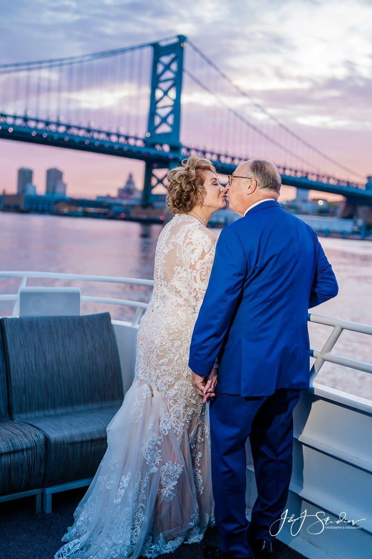 couple kiss in front of ben franklin bridge