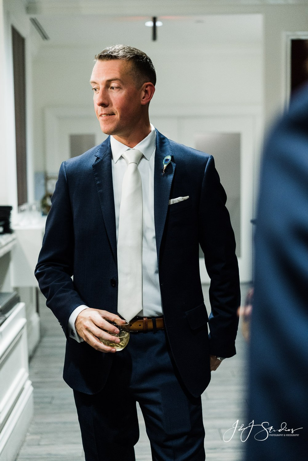 groom in blue navy suit by the black tux photo by j&j studios
