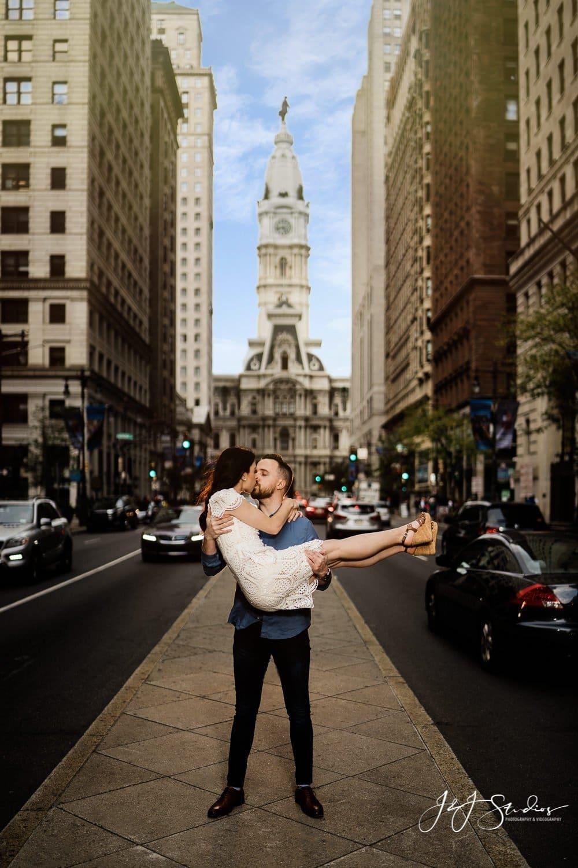 city hall broad street groom carrying bride by j&j studios