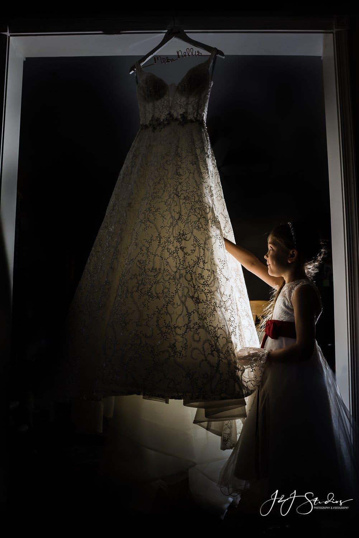 flower girl looking at wedding dress ramblewood country club wedding photo by john ryan j&J studios
