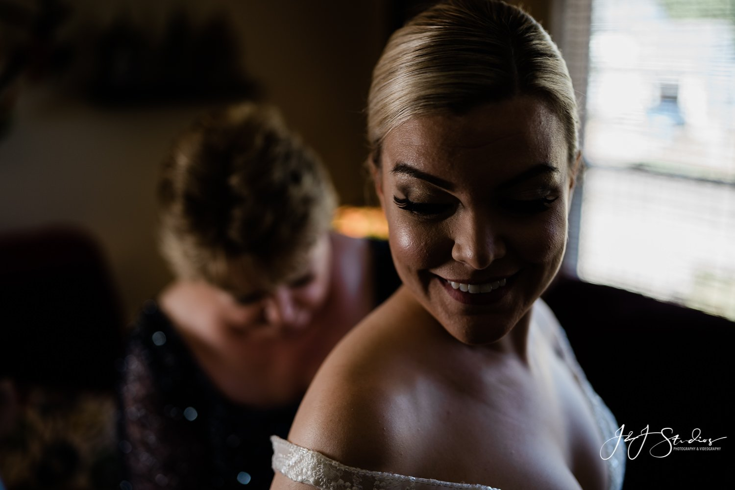 mother of the bride helps bride into dress ramblewood country club wedding photo by J&J Studios