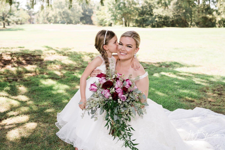 flower girl kisses bride on cheek