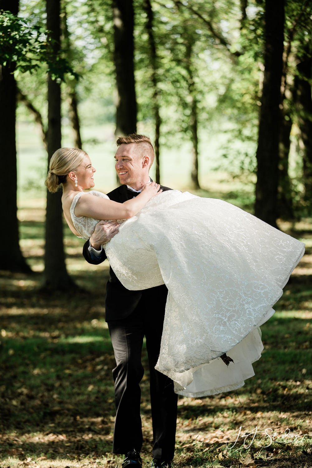 groom carrying bride through the forest
