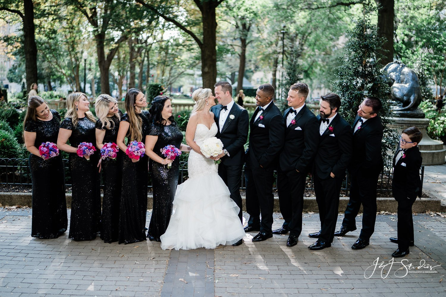 bride groom and bridal party in rittenhouse square by J&J Studios