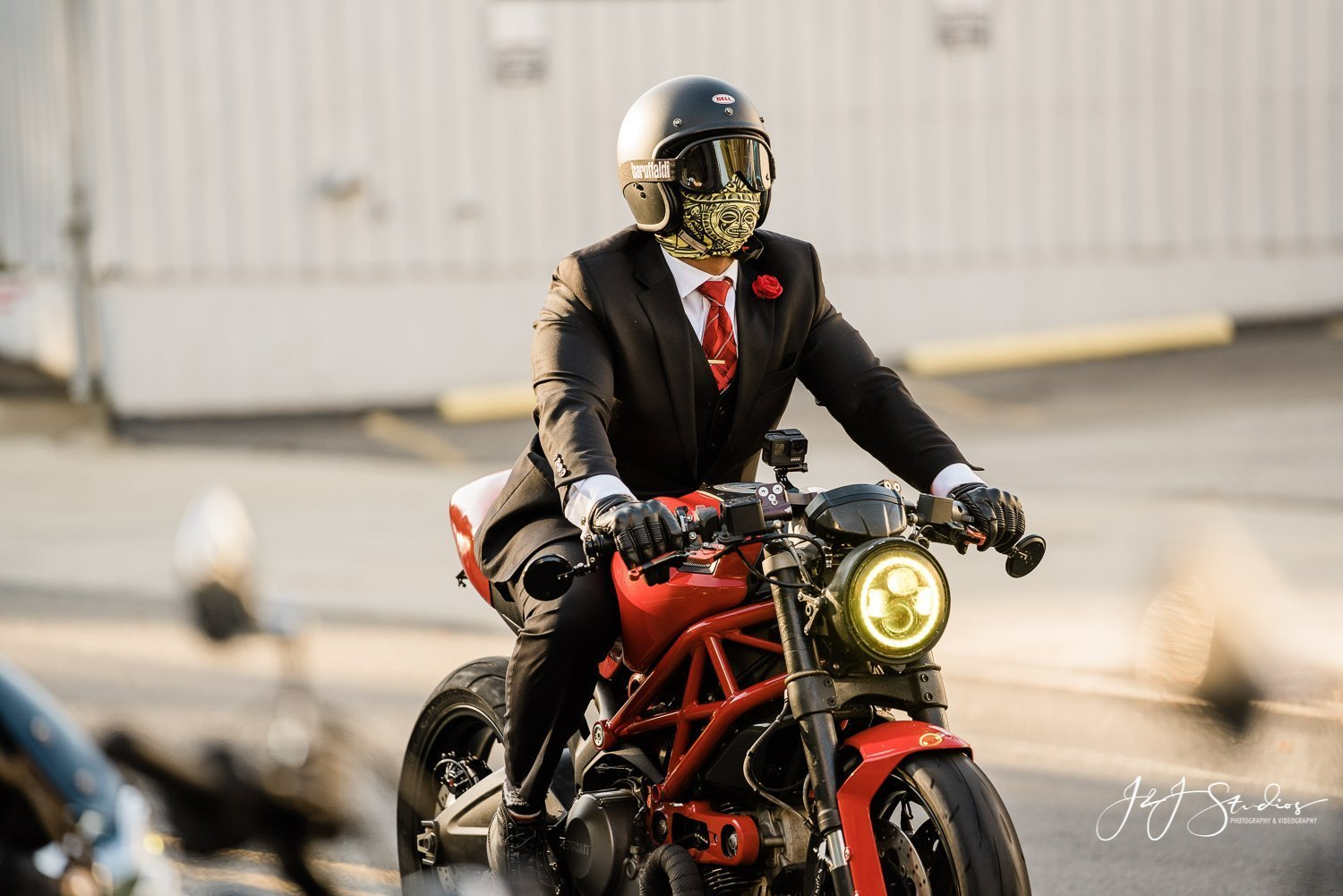 man in suit, helmet, gloves and red tie on red motorcycle