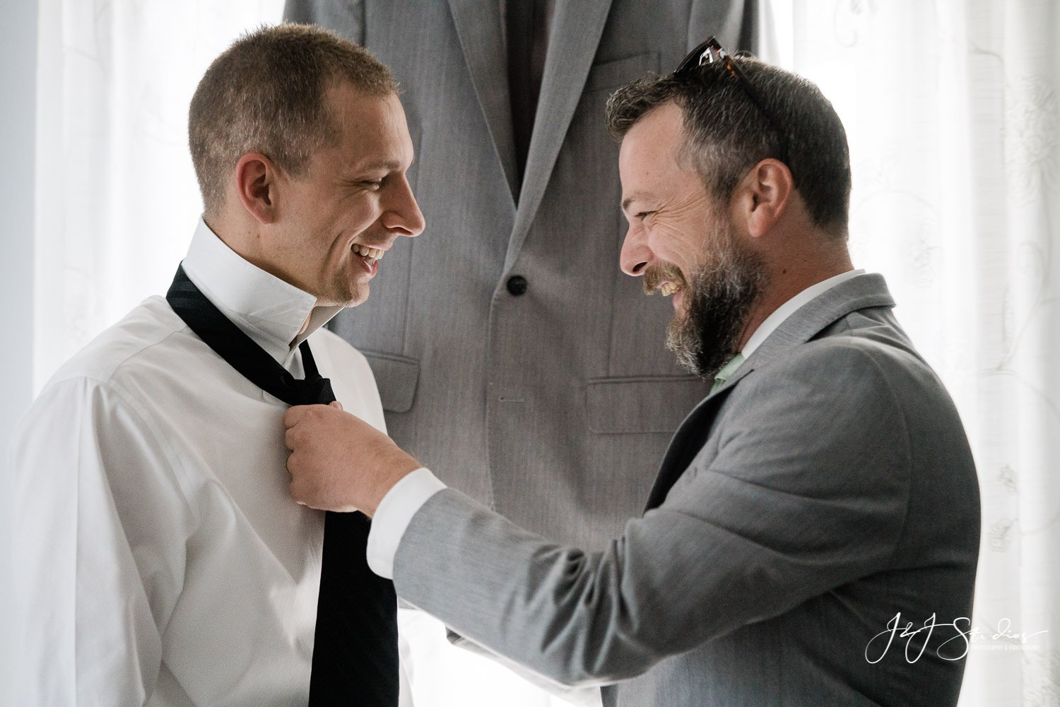 best man helping groom tie his tie baltimore maryland wedding