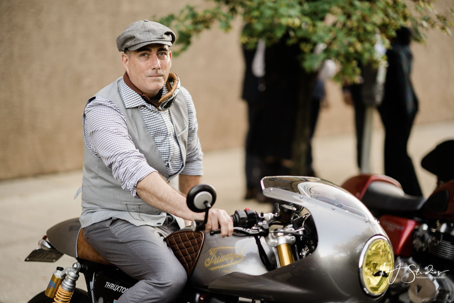 dapper man in hat on motorcycle