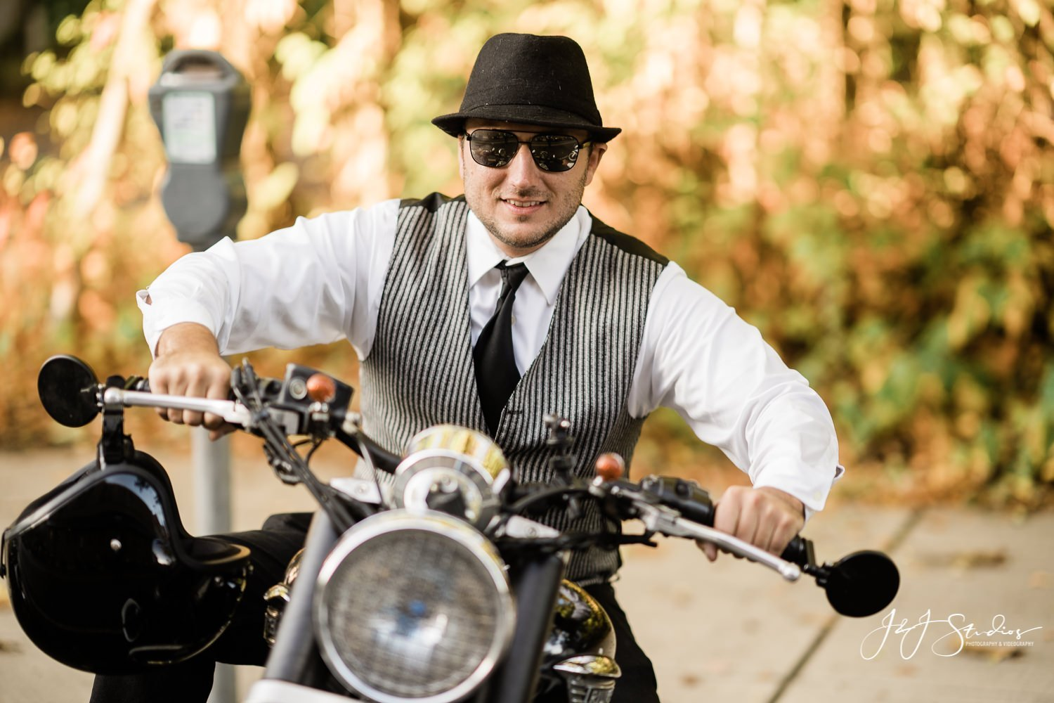 man in fedora and vest on motorcycle