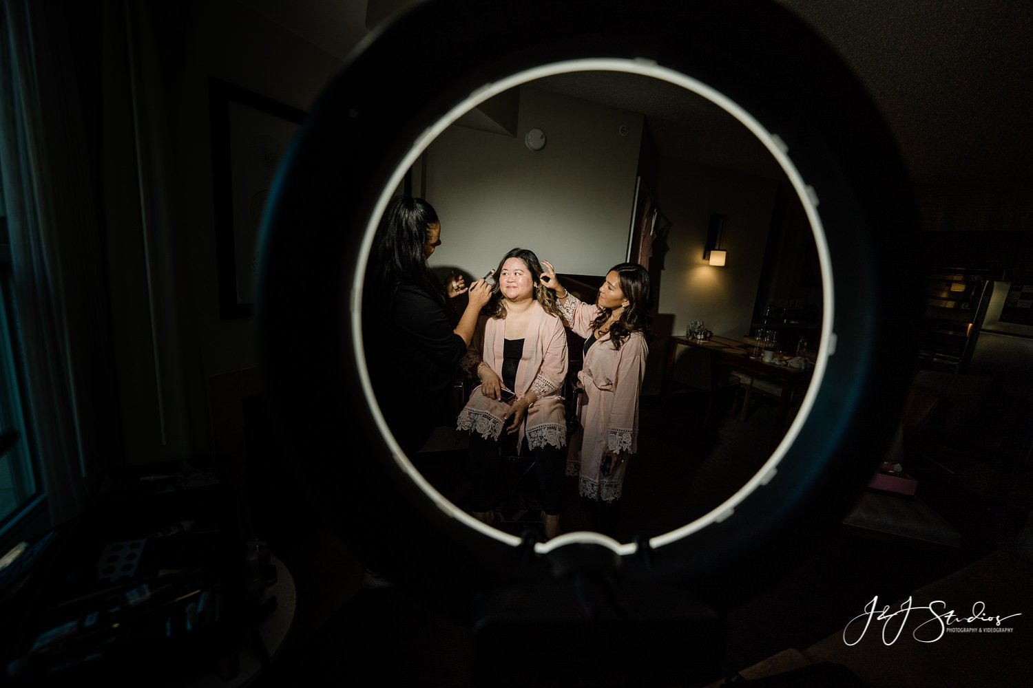 bridesmaid gets make up shot through make up artists ring light