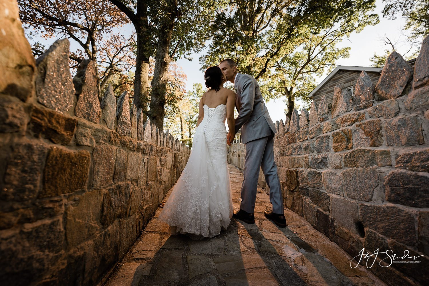 bride and groom walking up stone path at sunset photo by John Ryan J&J Studios