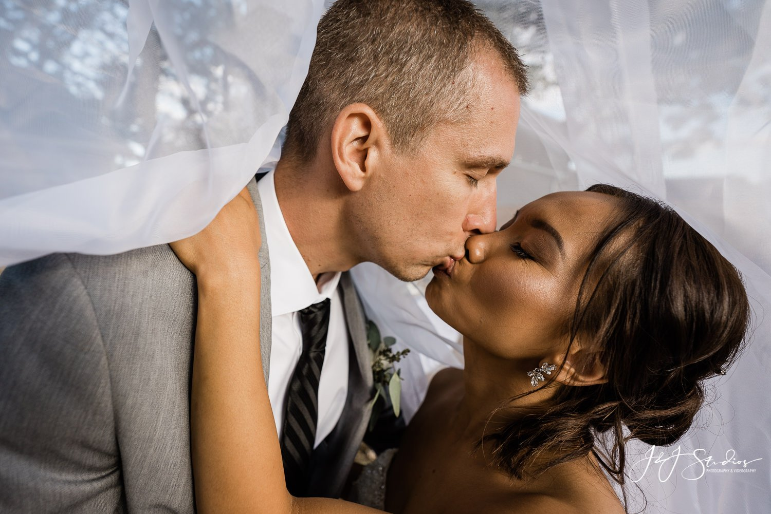 bride and groom kiss under veil baltimore wedding photographer