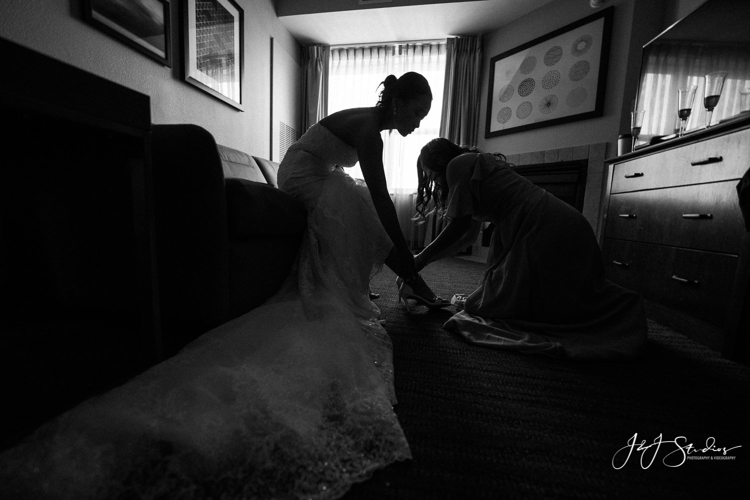 maid of honor helps bride get her heels on baltimore wedding photo by john ryan j&j studios