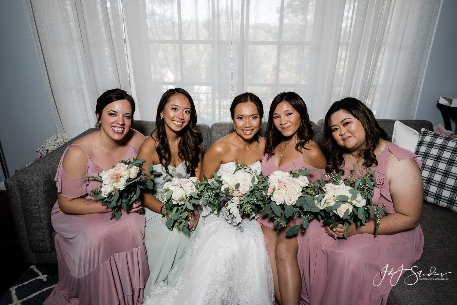bride and bridesmaids on couch before baltimore home wedding