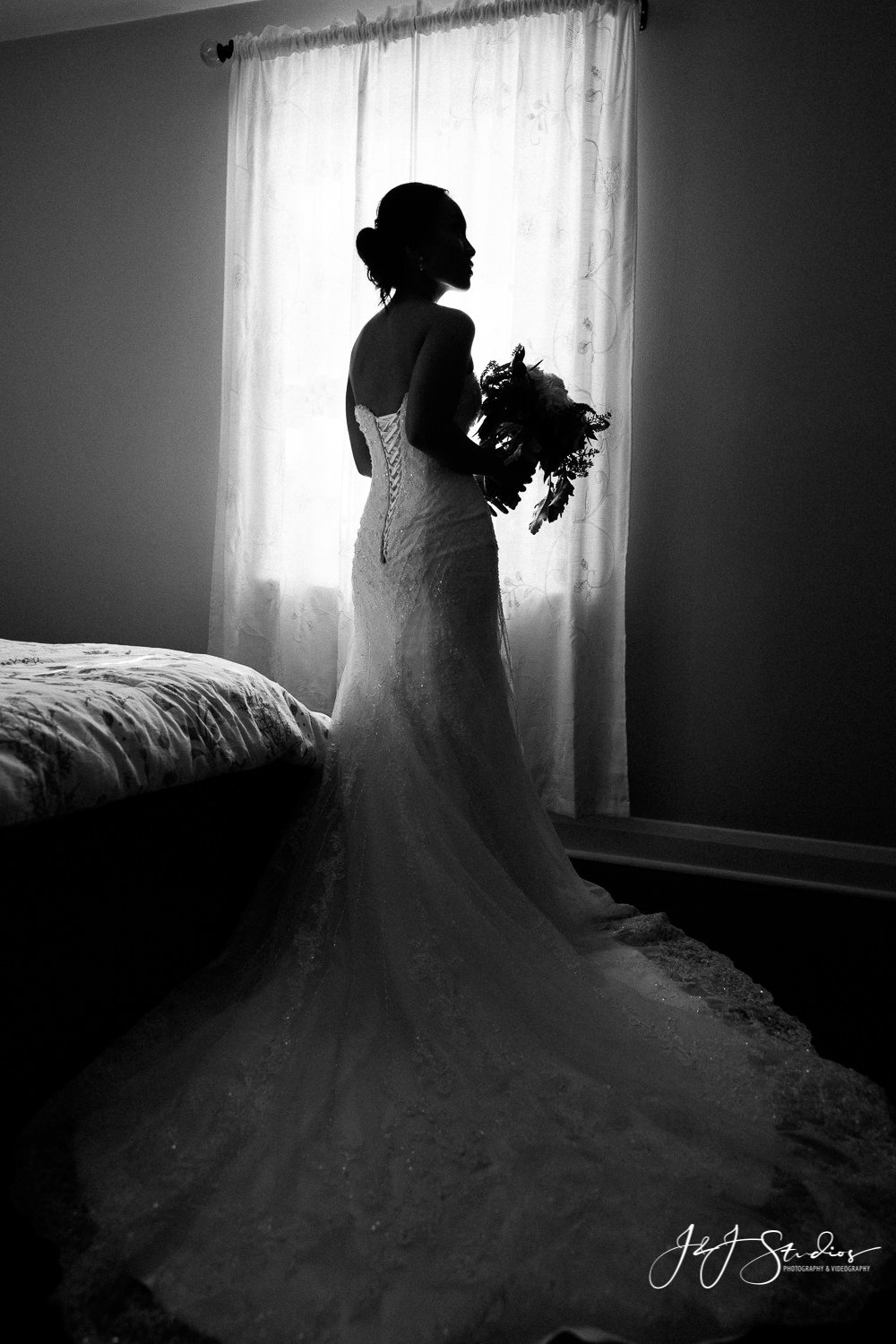 bride silhouette looking out window prior to her wedding at home