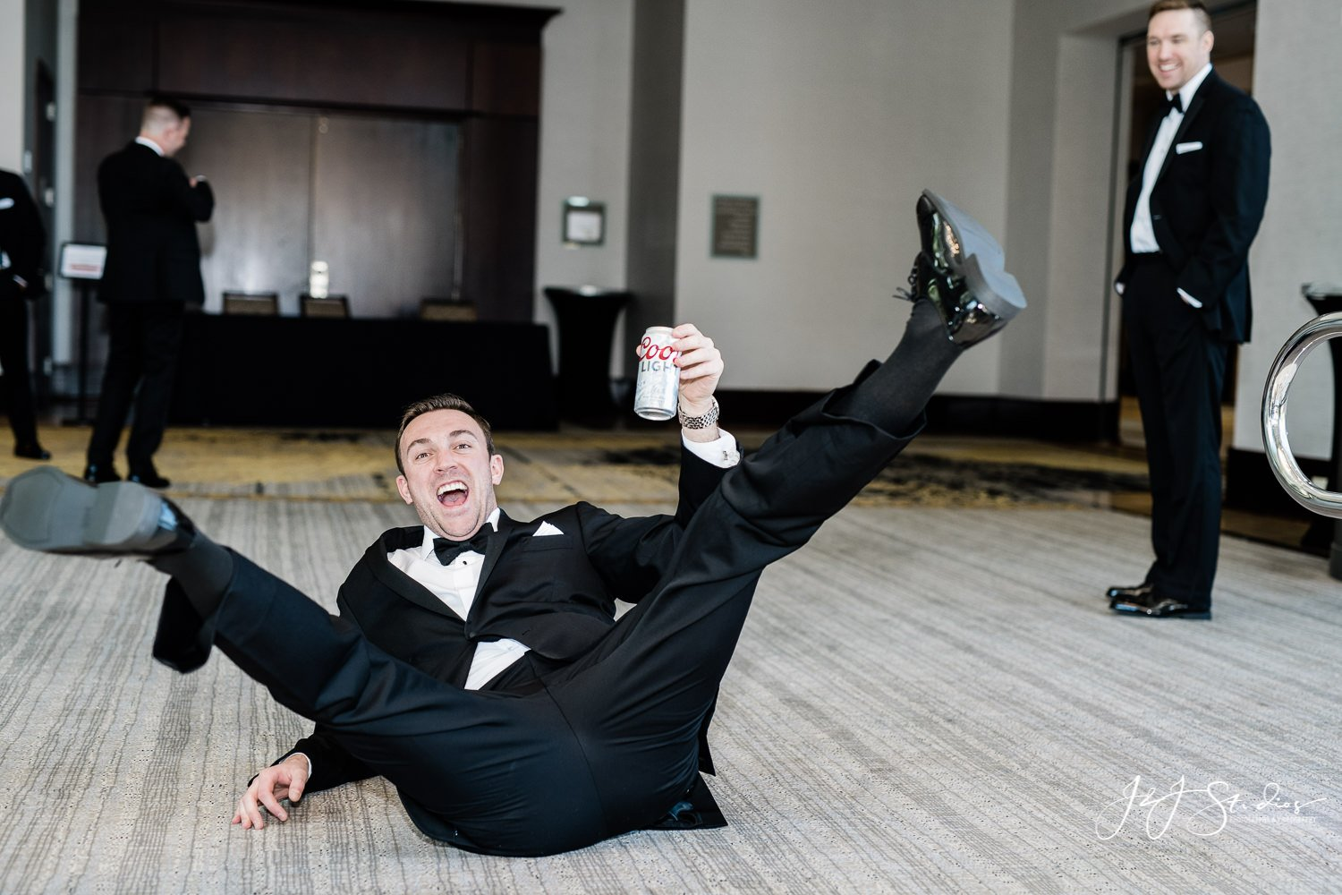 groomsmen drinking and doing spread eagle pose on floor with coors light bear photo by j&j studios