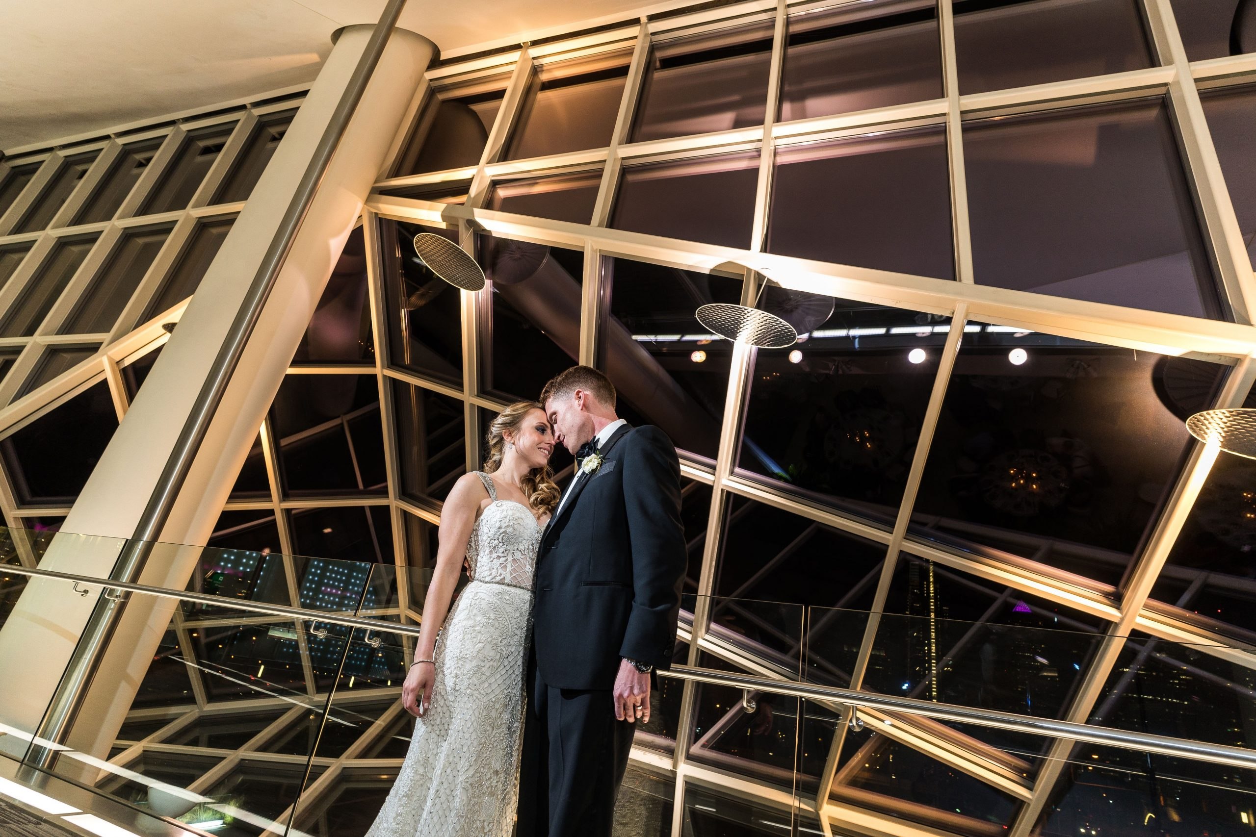 A newly married couple posing in front of the unique windows at JG Domestic at Cira Centre wedding venue