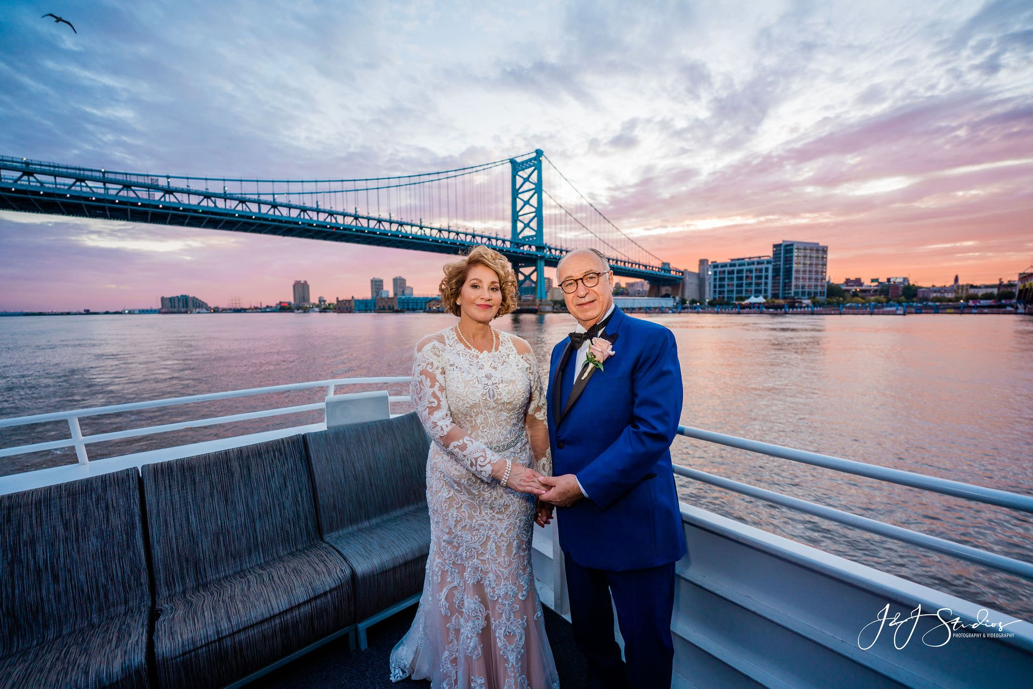 A couple stands on a boat with a bridge behind them on Delaware river They are aboard the Freedom Elite Yacht chart