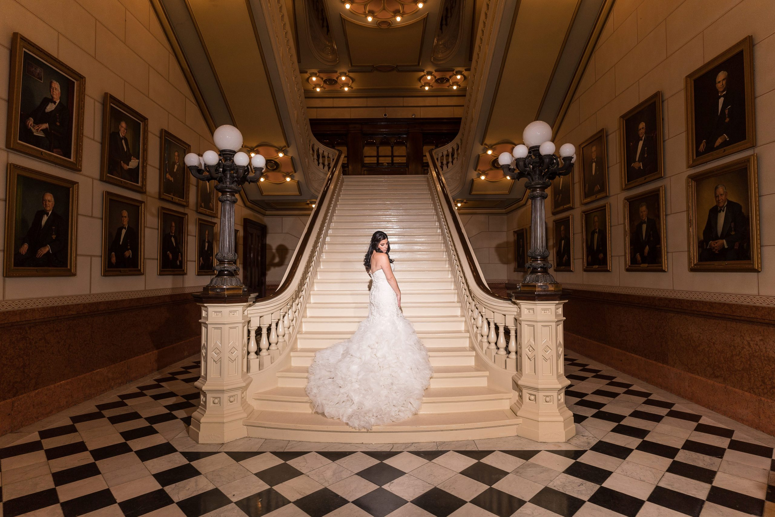 A young bride poses on the stairs at One North Broad a wedding venue in Philadelphia Pennsylvania