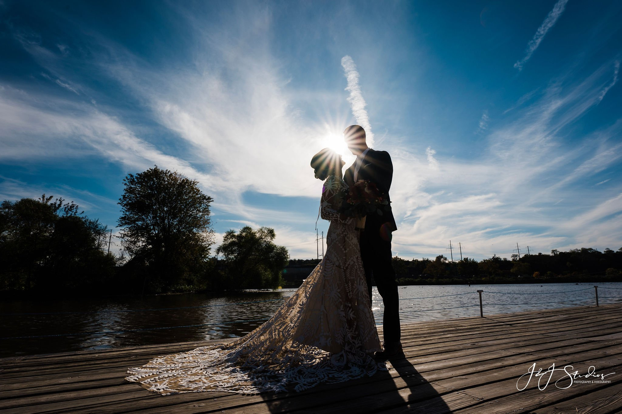 A couple on a pier at Boathouse Row in Philadelphia on their wedding day