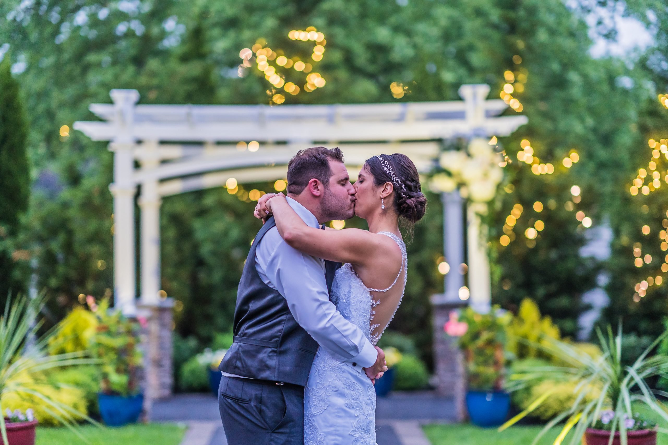 A newly married couple kisses in the garden at the Warrington Country Club Venue