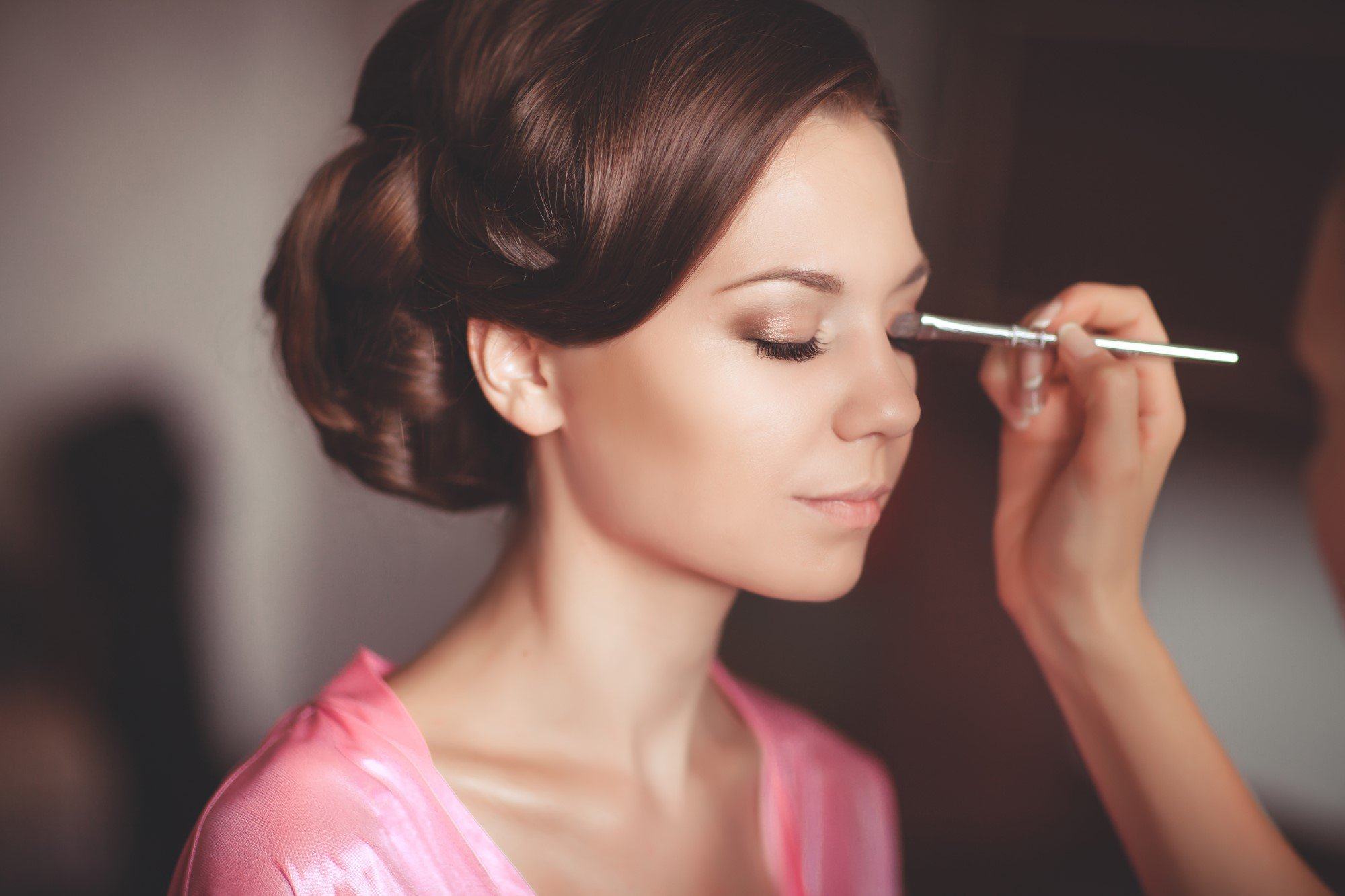 Woman getting eyeshadow before a wedding
