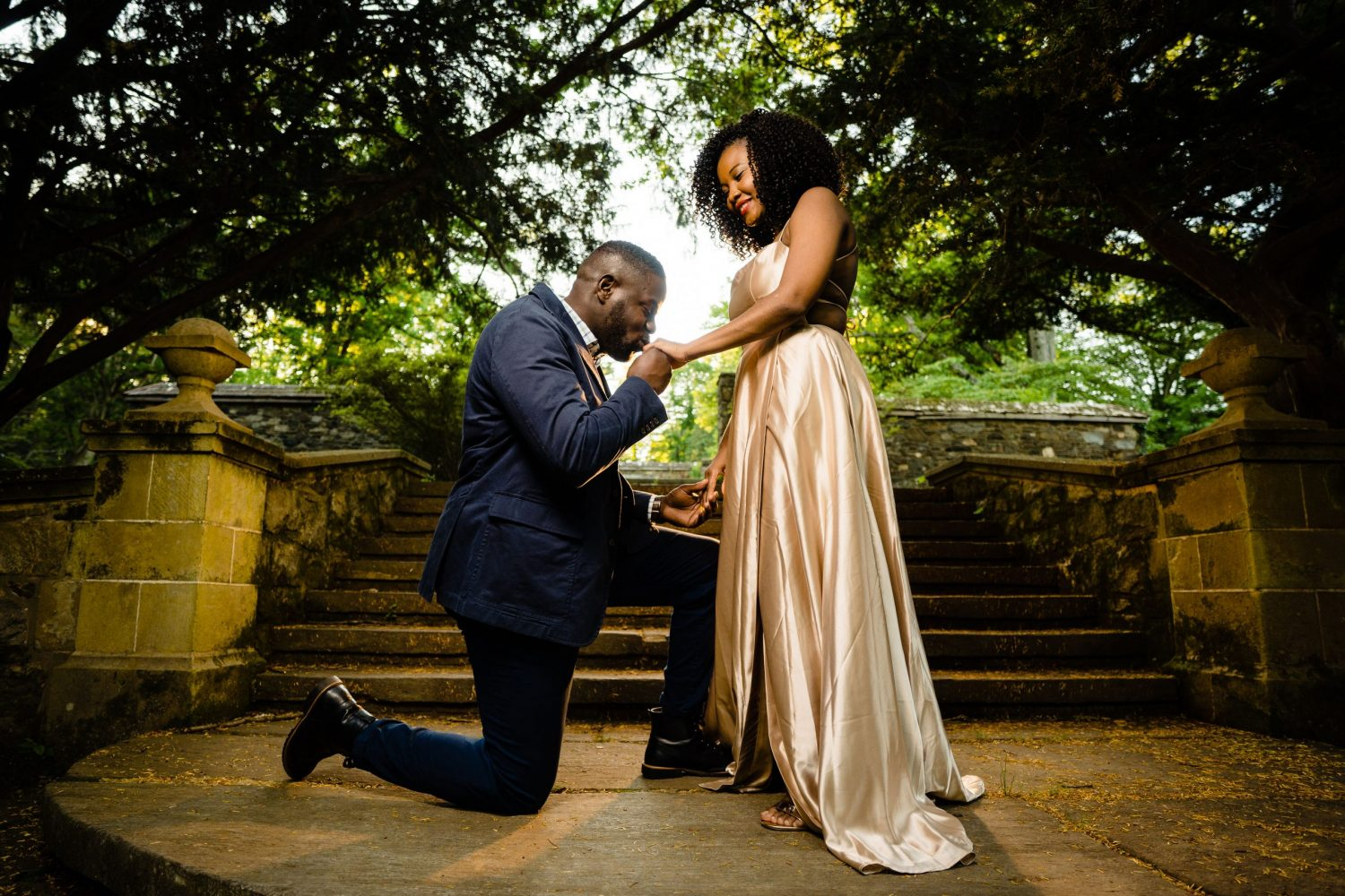 Kneeling down kissing hand stone stairs in background