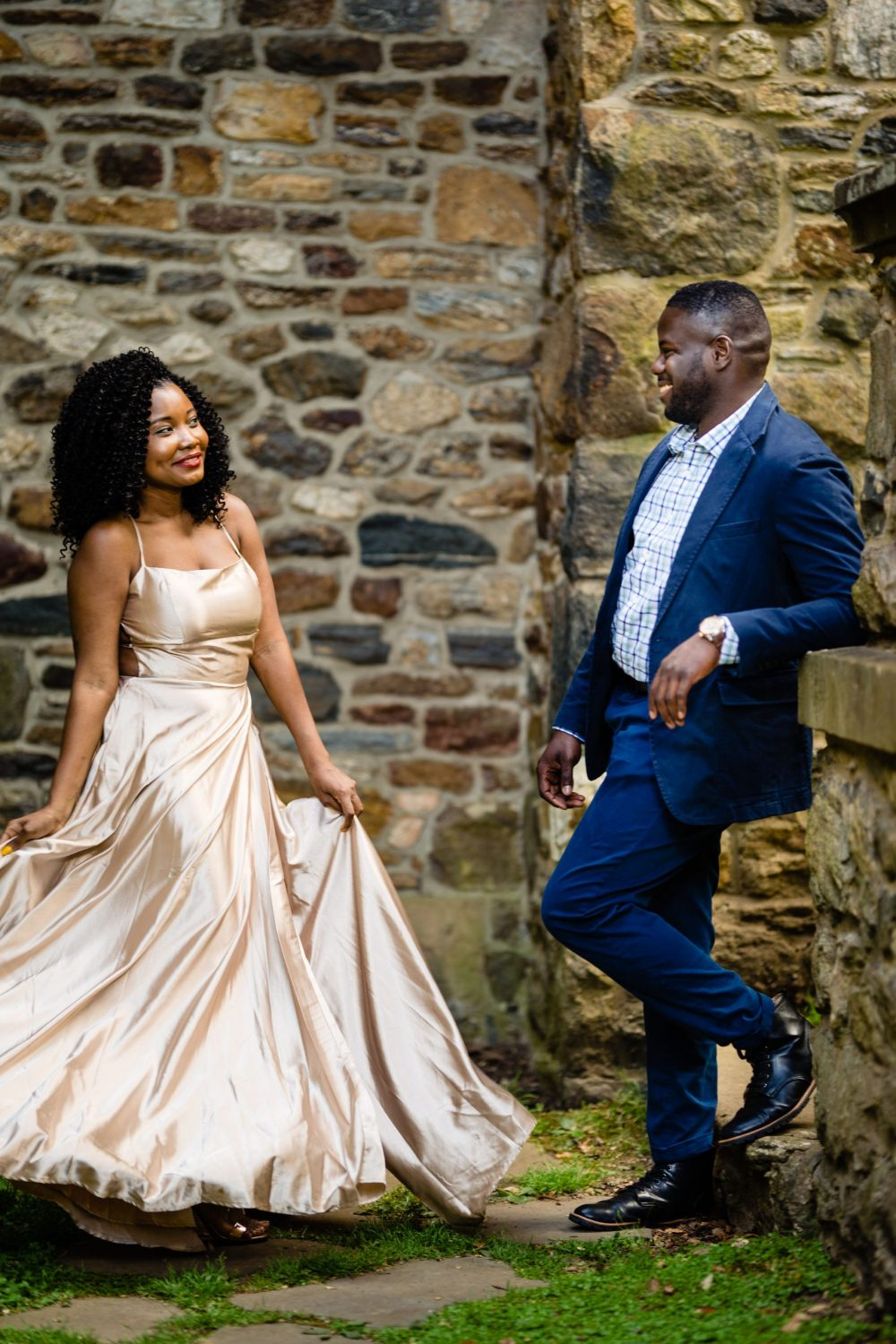 Stone wall and engaged couple twirling in dress
