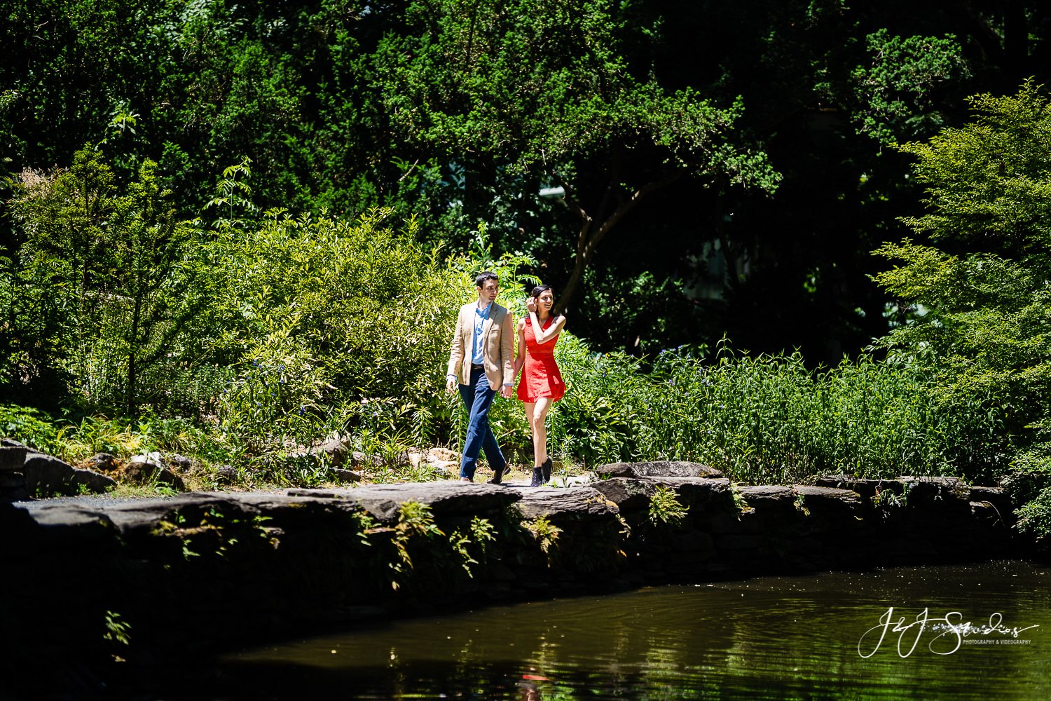 Surprise engagement walking through park in Philly