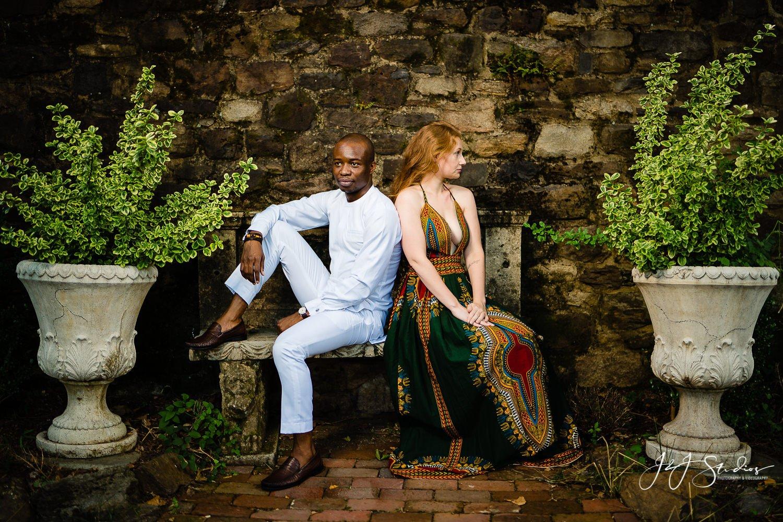 posing engaged couple cobblestone wall dress